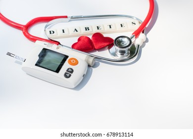 "Close up stethoscope, lancelet, red heart, glucose meter and word ""DIABETES"" on white background with copy space. Medicine, heart disease, diabetes, glycemia, health care and people concept."