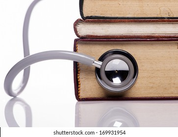 close up stethoscope on old book on white background
