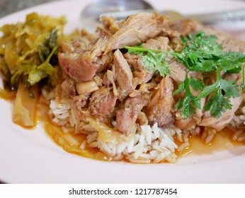 Close up of stewed pork leg with pickled cabbage on rice (Kao Ka Moo)