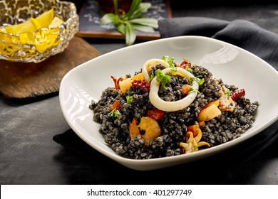 Close Up Still Life of Black Rice and Fresh Seafood Dish - with Squid Rings, Shrimp and Cuttlefish - Served in White Bowl on Table with Lemon Wedges