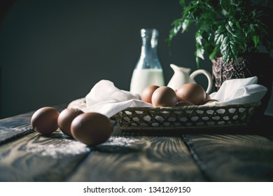 Close up still life of Chicken eggs in basket on rustic boards and dark background.