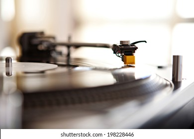 Close up still life detail view of a record player playing music with the needle touching the groove of the album against a sunny golden window in a music club interior. DJ equipment working in venue.