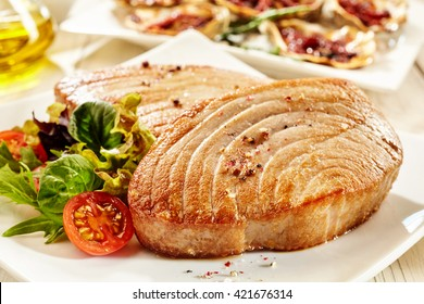 Close Up Still Life of Fried Tuna Steaks Served with Fresh Side Salad with Tomatoes on White Plate Amongst Other Dishes