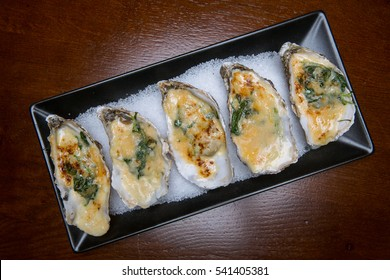 Close Up Still Life of Oysters with Cheesy Gratin Topping Served on Plate with Green Garnish on Rustic Wooden Table