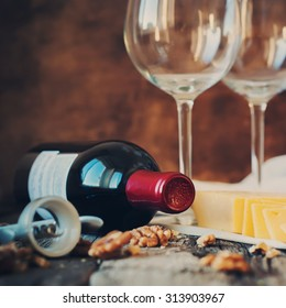 Close up Still Life with Red Wine, Walnuts, Cheese and Opener on Wooden Table. Country Style