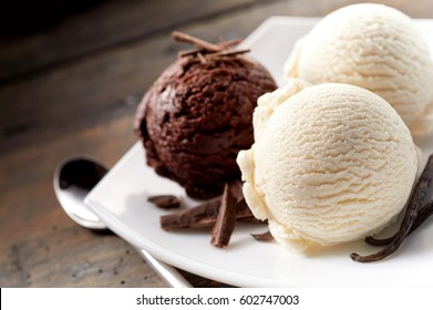 Close Up Still Life of Scoops of Chocolate and Vanilla Ice Cream with Chocolate Shavings and Vanilla Beans on Modern White Plate with Spoon on Rustic Wooden Table Surface with Copy Space
