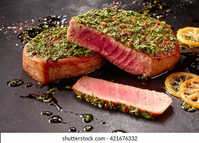 Close Up Still Life of Seared Tuna Steaks Topped with Fresh Pesto on Dark Gray Surface Dirtied with Oil and Lemon Slices