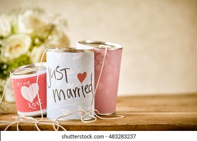 Close Up Still Life of Tin Cans Decorated with Congratulatory Messages and Tied with String for Dragging Behind a Car Following Wedding, Resting on Rustic Wooden Table with Copy Space