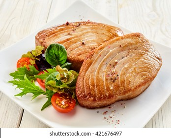 Close Up Still Life of Two Fried Tuna Steaks on Square White Plate with Seasoning and Fresh Green Salad with Tomato on Painted Wooden Table