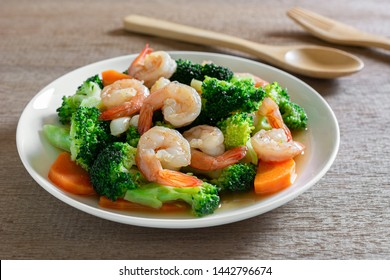 close up of stir fried broccoli with shrimps in a ceramic dish on wooden table. homemade style food concept.