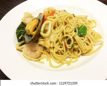 Close up stir fried spicy spaghetti with seafood , Spaghetti pad kee moa talay