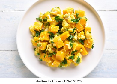 Close up of stir-fried pumpkin with eggs on plate over white wooden background. Pumpkin and egg stir fry in thai style. Top view, flat lay