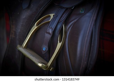Close up of a stirrup and horse saddle.