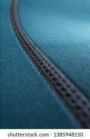 Close up of stitching along the seam of a blue neoprene surfing / scuba diving wetsuit