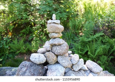 Close up of a stone cairn against a green background on the GR10 background in the Pyrenees, France