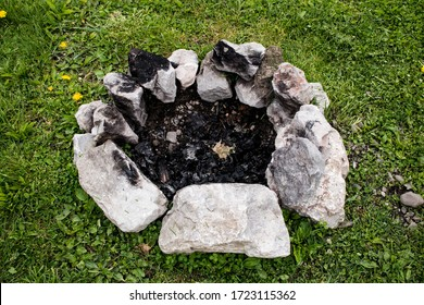 close up of stone fire pit in the middle of grass with black ashes in the center of the circle