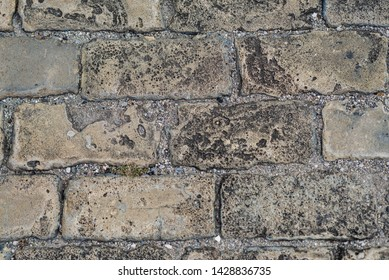 Close up stone pavement view from the top. Top view of stone pavement, texture. Granite cobblestoned pavement background