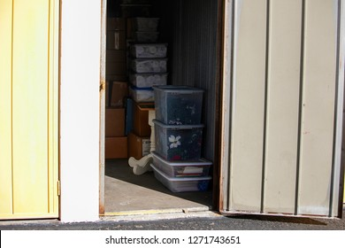 Close up of a storage unit with furniture and boxes in a secure self storage facility with multiple drive up units.