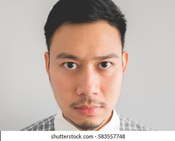 Close up of straight face of serious Asian man with light beard.