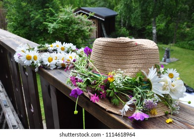 close up of a straw hat with a midsummer flower crown on it and a midsummer flower crown in the background