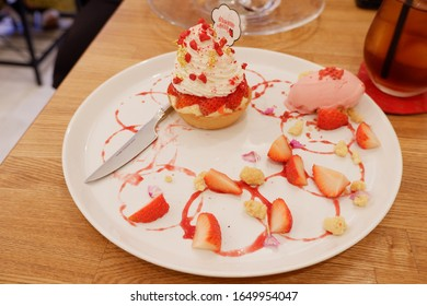 Close up to strawberry Chou cream decorating by strawberry and sauce on white plate from Osaka japan 24/02/2019