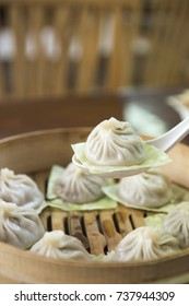 Close up of streamed Pork Dumplings Chinese food that called Xiao Long Bao on spoon.