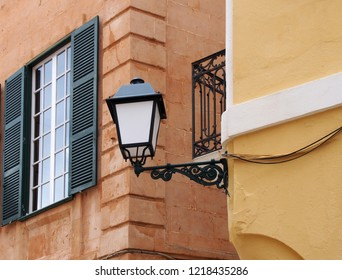 close up street corner view of an ornate old street lamp mounted on a painted yellow house with iron balcony and window with open wooden shutters