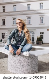 Close up street urban portrait of young stylish pretty blondie woman in fashion jeans in glasses sitting outdoors in the street . Beauty, student, freedom concept