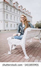 Close up street urban portrait of young fashion stylish pretty blondie woman in fashion jeans in glasses sitting outdoors in the street drinking coffee. Beauty, student, freedom concept