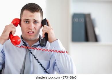 Close up of stressed businessman unable to cope with the telephone