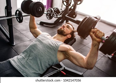Close up of a strong man doing push ups with the dumbells. He is consentrated only on doing that exercise and on nothing else. Cut view.