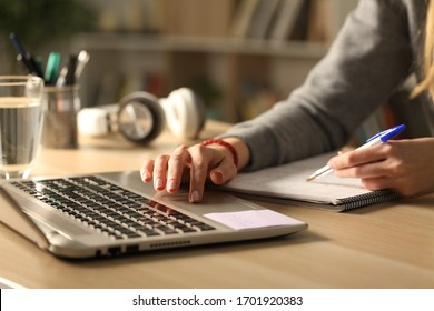 Close up of student girl hands comparing notes on laptop sitting on a desk at home at night