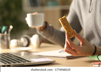 Close up of student girl hands holding coffee cup and cereal snack bar at night studying - Shutterstock ID 1774968125