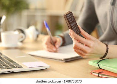 Close up of student girl hands holding chocolate snack bar studying at home - Shutterstock ID 1788733073