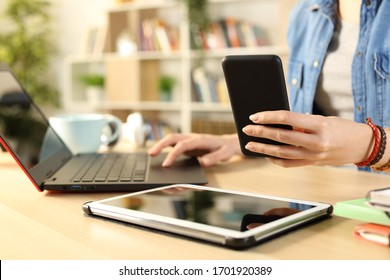Close up of student girl hands using multiple devices sitting on a desk at home
