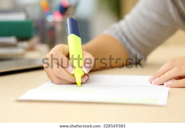 Close up of a student hand underlining a document on a desk at home