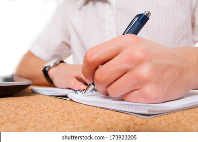 close up of student hand writing in exercise book