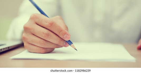 close up student man hand holding pencil for writing or doing homework on papersheet after reading or finish class at college , education concept