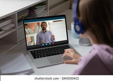 Close up student schoolgirl watching webinar, homeschooling concept, teenage girl wearing headphones using laptop, studying at home, making video call, African American teacher explaining