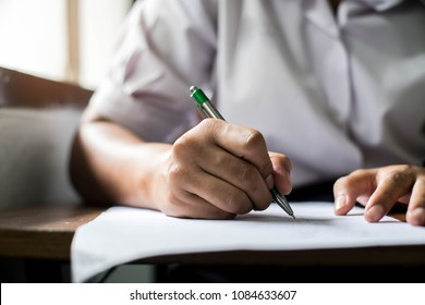 Close up Students writing and reading exam answer sheets exercises in classroom of school with stress.