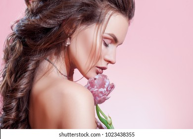 Close up studio beauty portrait of young beautiful woman with fresh, smooth, flawless skin, nude make up, greek braid, bridal hairstyle. Model posing on pink background, holding flower. Copy space