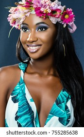 Close up studio beauty portrait of young african woman wearing flower garland.Young girl with long hair and charming smile against dark blue background.