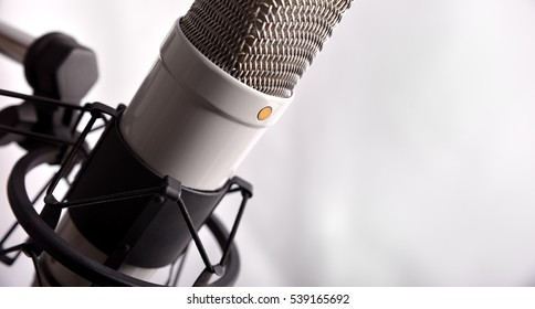 Close up studio condenser microphone with pop filter and anti-vibration mount isolated white. Side view