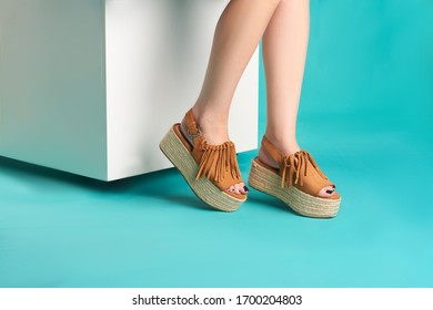 Close up studio photo of brown high sandals of a woman sitting on a white cube with an aqua background.