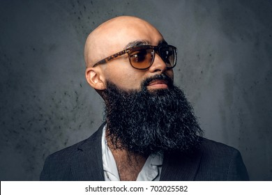Close up studio portrait of Arabic bearded shaved head male in sunglasses.