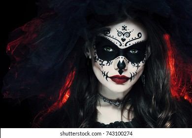 close up studio portrait of beautiful woman with halloween sugar skull makeup in red and black