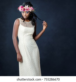Close up studio portrait of elegant young african bride wearing colorful flower garland.Woman on white designer wedding dress against dark background.
