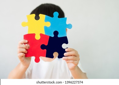 Close up studio portrait : A little child holding a puzzle symbol of Public awareness for autism spectrum disorder. World Autism Awareness Day, Caring, Speak out, Campaign, Togetherness. Isolated.
