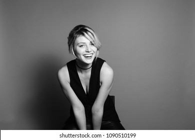 Close up studio portrait of a pretty blonde woman, laughing and looking at camera, against plain studio background