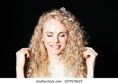 Close up studio portrait of a pretty curly blonde woman, eyes closed, both hands up, against plain studio background